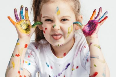 Little girl covered in paint making funny faces. Kindergarten kid. Prankster.